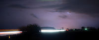 Moving Vehicles Drive Away From an Electrical Storm at Night
