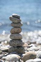 Steinturm am Strand mit Wasser im Hintergrund