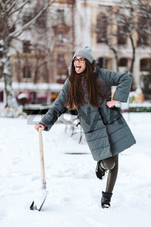 Beautiful girl in winter fashion clothes with a shovel