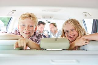 Zwei lachende Kinder auf dem Rücksitz
