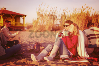 Couple enjoying with friends at sunset on the beach