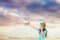 Nice girl playing with knitted airplane toy