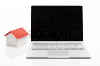 Laptop und Haus