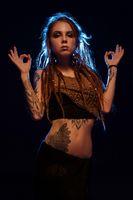 Girl with henna bodyart and dreadlocks view