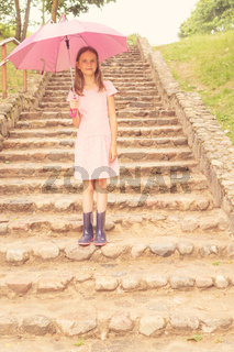 Girl with umbrella stands on the stairs