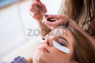 Young woman getting eyelash extension