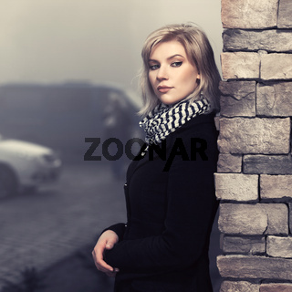Fashion blond woman in black coat leaning on wall in city street