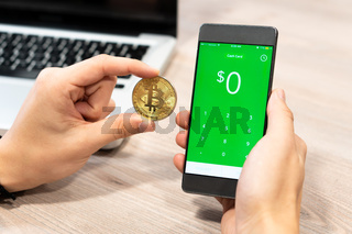 Cash App by Square inc displayed on smartphone held by human hand next to Bitcoin coin and computer laptop - Slovenia 13.02.2019