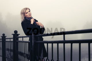 Young fashion woman in black coat leaning on railing outdoors