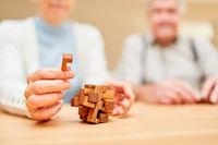 Senioren machen ein Geduldspiel mit Holzpuzzle