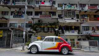 A classic VW Beetle parked in front of flats in a street in central Kuala Lumpur. A popular classic car to see in Malaysia.