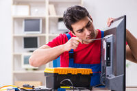 Professional repair engineer repairing broken tv