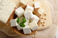 Flat lay view at Soy Bean curd tofu in wooden bowl on kitchen table. Non-dairy alternative substitute for cheese