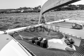 Sporty man relaxing on a luxury catamaran sailing boat.