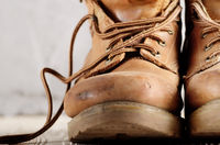 Yellow leather used work boots on concrete background closeup. Place for text