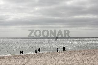 Wanderer am Strand im Gegenlicht