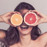 Woman holding halves of citrus fruits