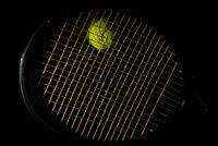 Tennis racket and ball on black