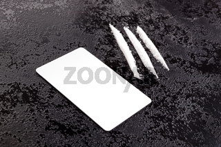 Cocaine lines with card on dark surface.