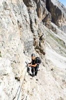 attractive blonde female mountain climber in the Dolomites of Italy
