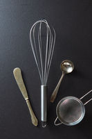Set of kitchen tools knife, whisk, sieve and spoon on black concrete background with copy space. Top view