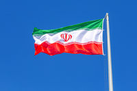 Flag of Iran waving in the wind against the sky