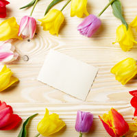 Frame of colorful tulips with blank greeting card on natural wooden background with space for text