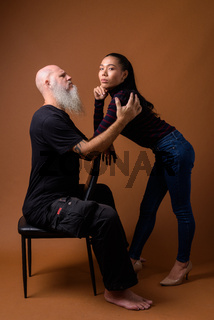 Mature bearded bald man with young Asian transgender woman