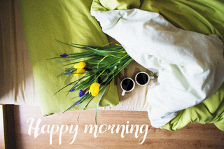 two cups of coffee and a bouquet of beautiful flowers lie in bed-inscription happy morning