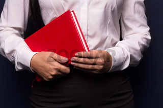 Smiling business woman holding red notebook