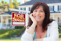Middle Aged Woman In Front of House with Sold For Sale Real Estate Sign In Yard