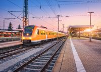 Passenger high speed train on the railway station at sunset