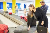 Geschäftsfrau und andere Reisende holen ihr Gepäck ab