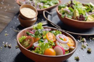 Vegetable salad of lettuce, cherry tomatoes, radish, cucumber, onion and basil on slate stone tray