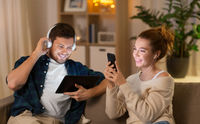 couple with gadgets listening to music at home
