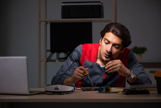 Young handsome repairman repairing computer