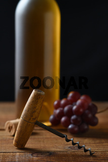 Closeup of an antique cork screw with out of focus white wine bottle grapes and cork in the background