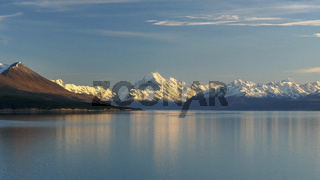 early morning wide shot of mt cook and a calm lake pukaki