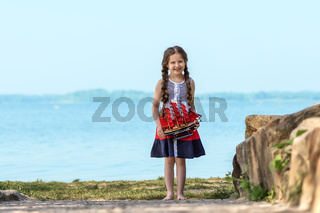 Portrait of a happy little girl by the lake. In her hands she holds a toy sailboat with scarlet sails.