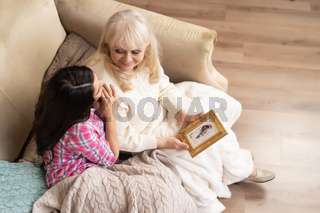 Mother and daughter look at portrait in frame