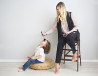 Mother and daughter doing make up oto each other