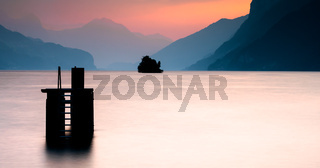 sunset over mountain lake with silhouette of diving platform and island and mountains