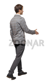 Back view of a walking businessman who stretches his hand for a handshake.