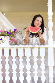 Girl on a wooden porch with watermelon