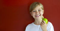 Happy blond little girl with green apple by the red wall