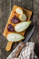 Halved fresh bulbs. Cut onions and knife.