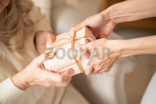 Close-up of women' hands holding a gift box