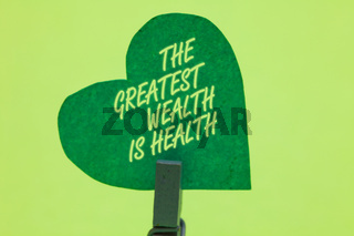 Conceptual hand writing showing The Greatest Wealth Is Health. Business photo showcasing being in good health is the prize Take care Clothespin holding green paper heart romantic message ideas.
