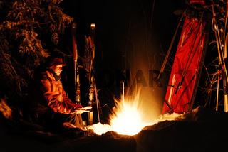 Frau waermt sich die Haende am Lagerfeuer