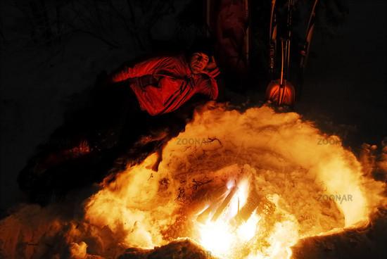 Mann liegt am Lagerfeuer